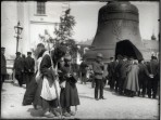A bearded man with a sack and a long stick leans over next to a young boy while a queue of people form next to a large bell behind