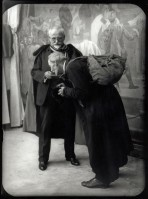 Dressed in a suit and a cape, Mucha holds out a dish for an elderly man with a long coat and a rucksack who bends over and touches the dish with his face