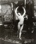 Nude in fifth position balancing on her left leg holding her right foot just behind her with both arms arched above her head