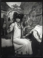 Model in a white embroidered tunic and a black frilly headpiece sits on a wite rug on a couch in front of an ornate gilt mirror