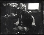 Seated model in a velvet smoking jacket holding a pipe to his mouth and reaching out with his right arm to a table behind him