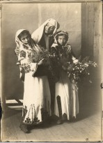 A woman in a white headdress stands with her arms around two girls in embroidered tunics holding bunches of flowers