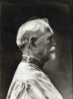 Mucha dressed in a traditional Czech shirt with head and shoulders seen in profile against a dark background