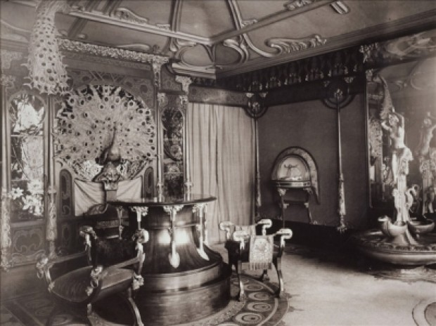 A black and white general view of the boutique interior with a peacock decoration on the far wall, a wooden circular counter with 2 elaborate stools and a presentation case and water feature on the right wall