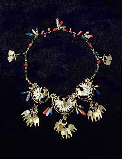 An ornate gold necklace with three circular motifs with doves and semi-precious coloured beads and droplets throughout the chain