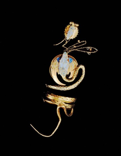Gold snake wrapped around three times with a stylised blue face attached to a chain with a second snake face motif