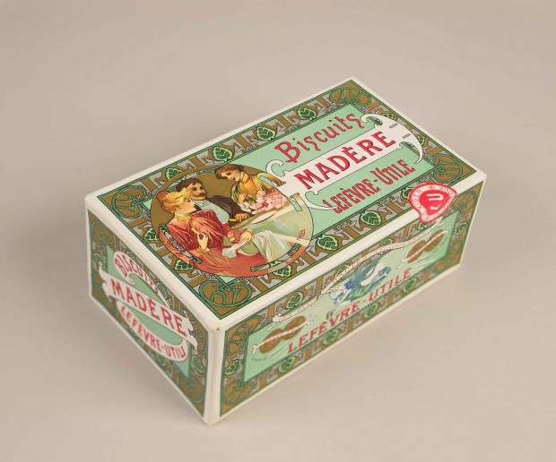 A rectangular box seen from above with an image of two elegantly dressed women and a man sitting at a table eating biscuits and a decorative vegetal pattern in gold, green and grey with the words 'Biscuits Madère Lefèvre-Utile.