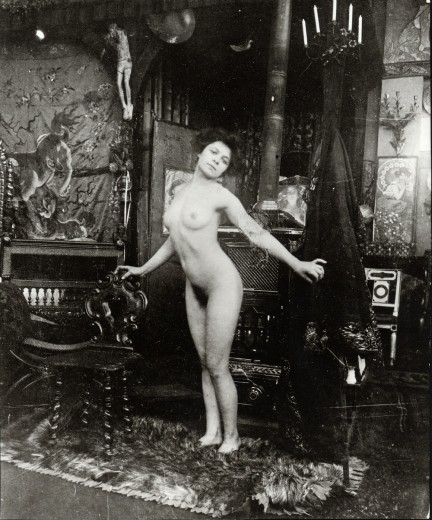 Nude leaning her chest forwards with both arms outstretched diagonally behind her back