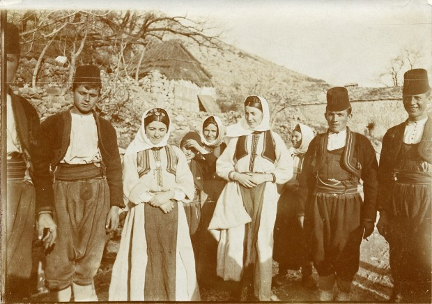 A group of four men, four women, and a small boy stand in a line in front of a stone settlement