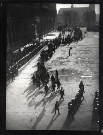 A procession of men through a Paris street (seen from above) with deep shadows cast from top right to bottom left