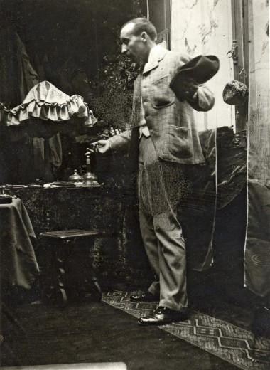 Gauguin stands side-on next to a window holding a hat in his left hand and looking down at the floor