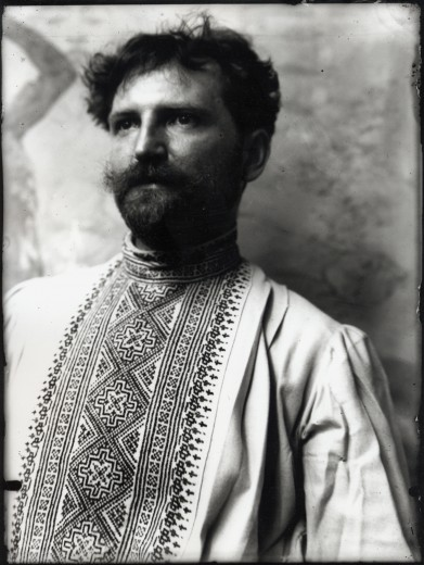 Head and torso self-portrait of Mucha dressed in a traditional Czech shirt looking out to the right of the camera
