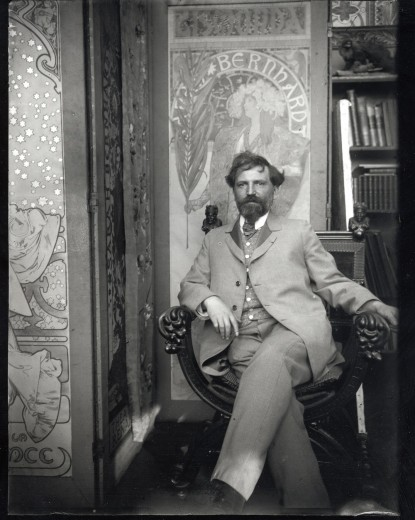 Mucha dressed in a suit seated in an ornate chair in front of 3 Sarah Bernhardt posters, looking at the camera
